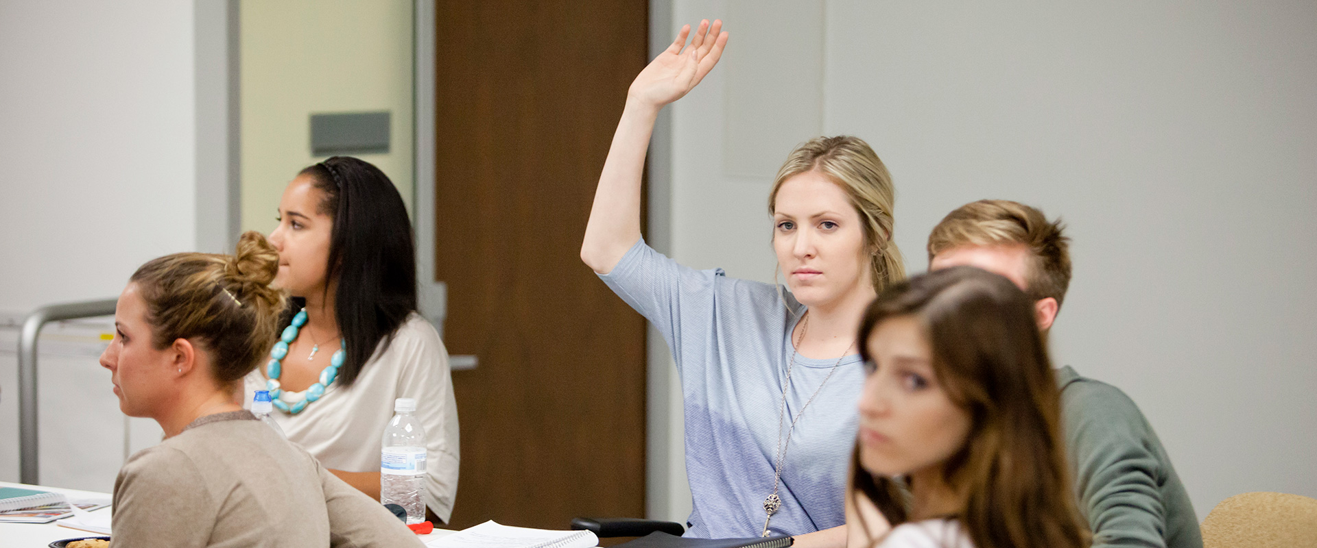 A student raising her hand in class