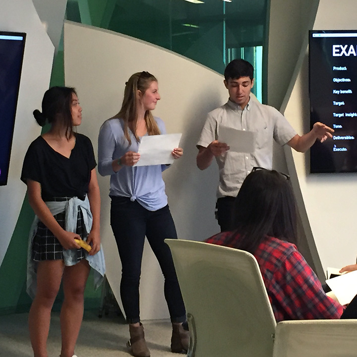Three students giving a presentation in front of several LCD screens